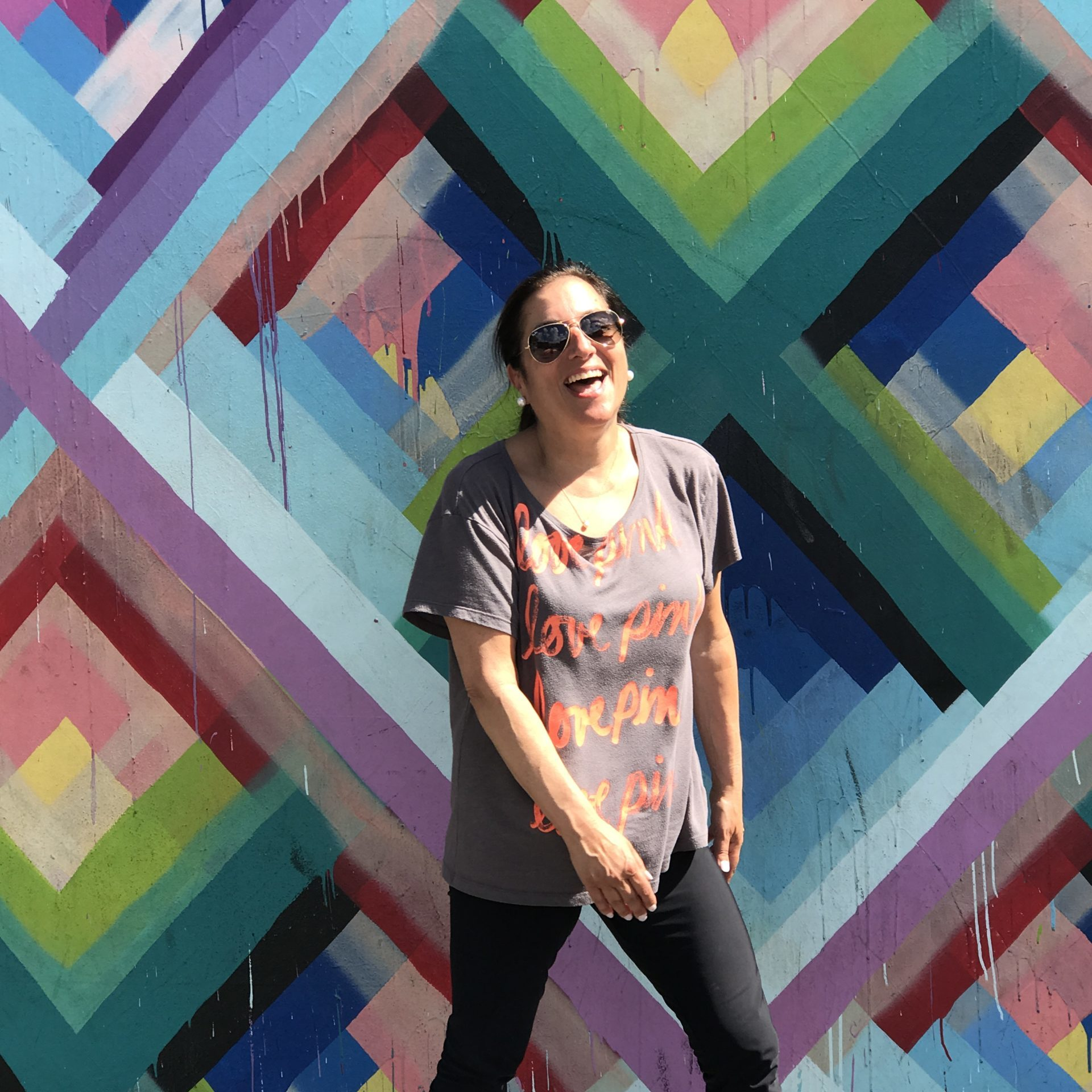 A photo of Shelley who has brown hair pulled back, and wearing sunglasses in front of a brightly colored background.