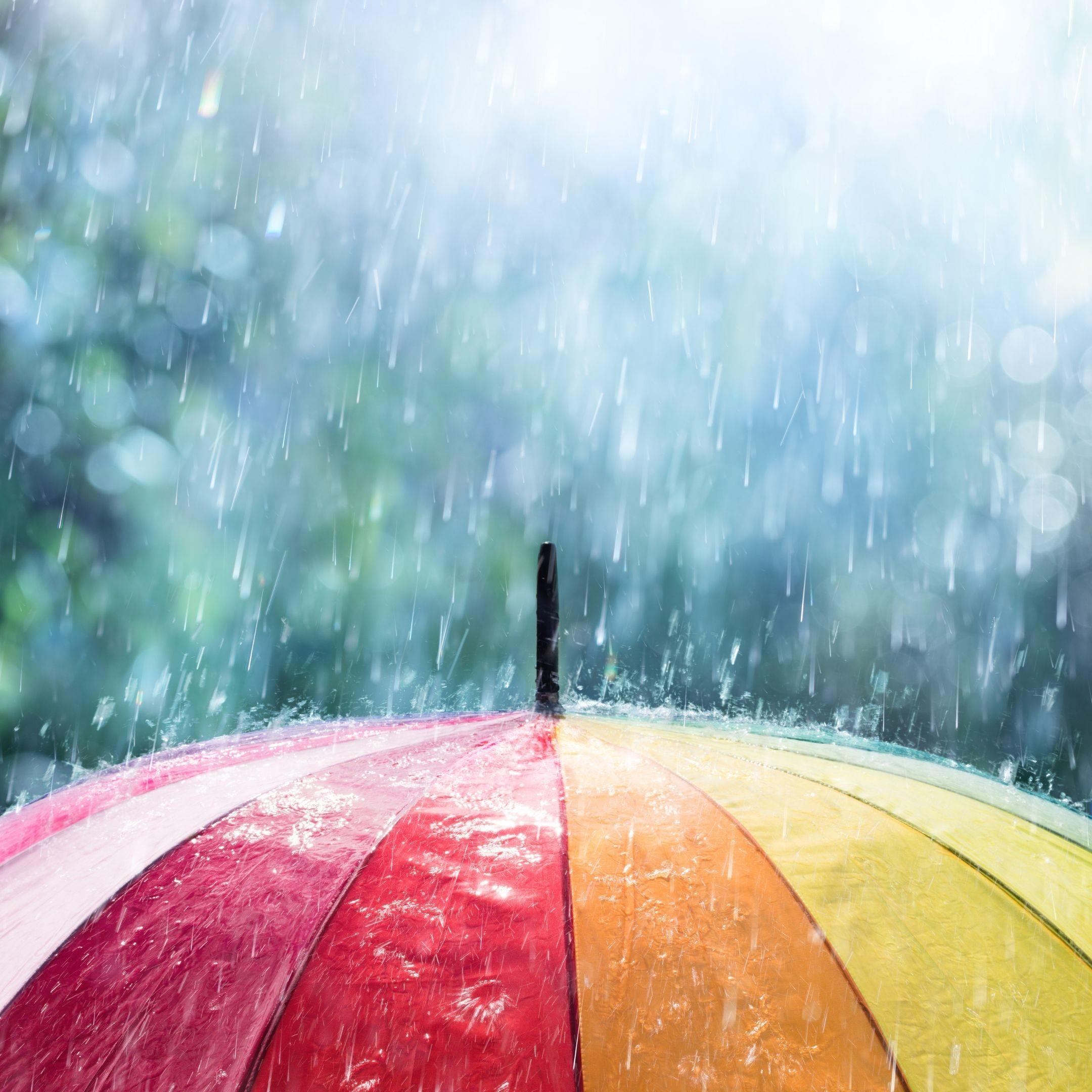 Colorful umbrella with rain falling on top