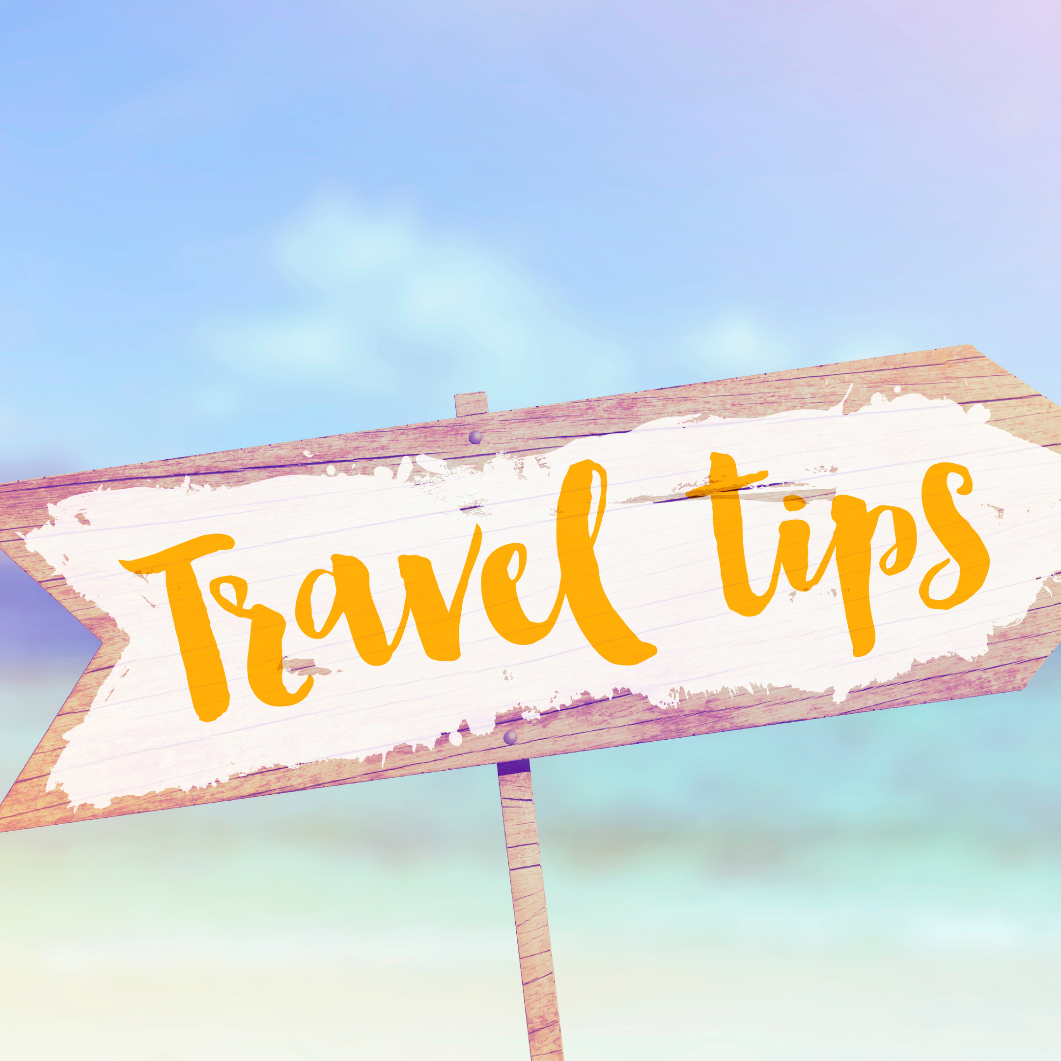 Wooden sign in front of beach scene with travel tips written on the sign